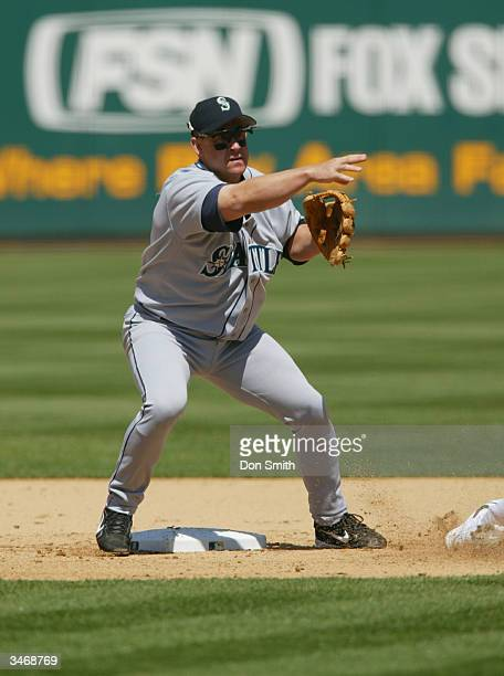 Second baseman Bret Boone of the Seattle Mariners throws the ball to first base during the game against the Oakland A's at the Network Associates...