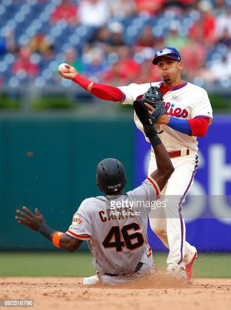 Second baseman Cesar Hernandez of the Philadelphia Phillies gets the force out on Orlando Calixte of the San Francisco Giants and throws to first...