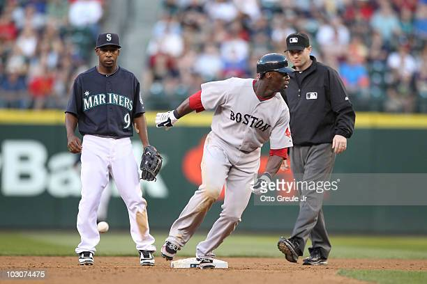Second baseman Chone Figgins of the Seattle Mariners watches the throw from left fielder Michael Saunders bounce past second base as Mike Cameron of...