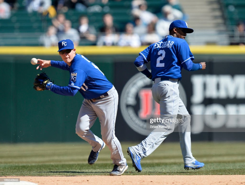 Second baseman Chris Getz #17 of the Kansas City Royals (L) bobbles the ball on an infield single hit by Alex Rios #51 of the Chicago White Sox as shortstop Alcides Escobar #2 runs by during the sixth inning on April 4, 2012 at U.S. Cellular Field in Chicago, Illinois.