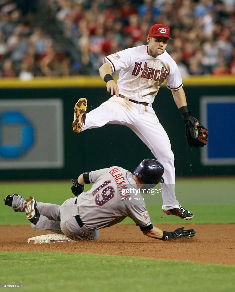 Second baseman Chris Owings #16 of the Arizona Diamondbacks leaps over Charlie Blackman #19 of the Colorado Rockies after throwing to first to complete a double play during the first inning of a MLB game at Chase Field on July 4, 2015 in Phoenix, Arizona.