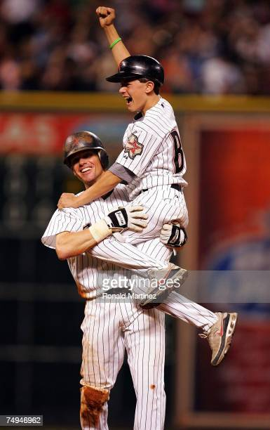 Second baseman Craig Biggio of the Houston Astros picks up his son, Conor after getting his 3,000th career hit against the Colorado Rockies in the...