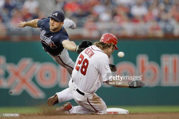 Second baseman Dan Uggla of the Atlanta Braves misses the ball as Jayson Werth of the Washington Nationals steals second base during the second...