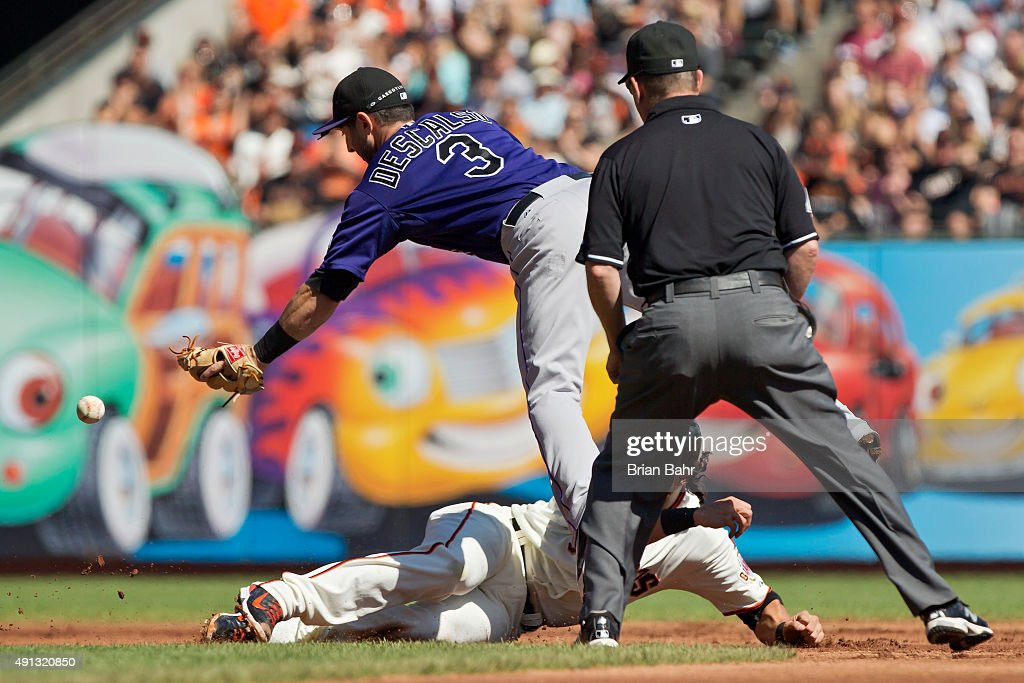Second baseman Daniel Descalso #3 of the Colorado Rockies dives for the bouncing ball as center fielder Angel Pagan #16 of the San Francisco Giants dives back to second after running past the base on a single by Kelby Tomlinson in the first inning at AT&T Park on October 4, 2015 in San Francisco, California, during the final day of the regular season.