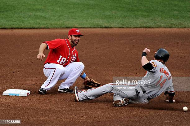 Second baseman Danny Espinosa of the Washington Nationals tries to tag out Nolan Reimold of the Baltimore Orioles after he steals in the seventh...