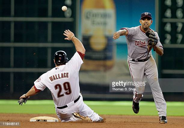 Second baseman Danny Espinosa of the Washington Nationals turns a double play on Brett Wallace of the Houston Astros in the 10th inning on July 20...