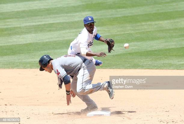 Second baseman Dee Gordon of the Los Angeles Dodgers collides with baserunner Yan Gomes of the Cleveland Indians after Gordon forced Gomes and threw...