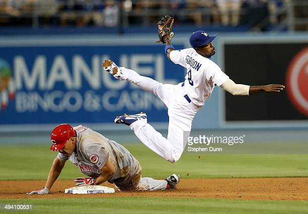 Second baseman Dee Gordon of the Los Angeles Dodgers watches his throw to first as he goes over baserunner Donald Lutz of the Cincinnati Reds in the...