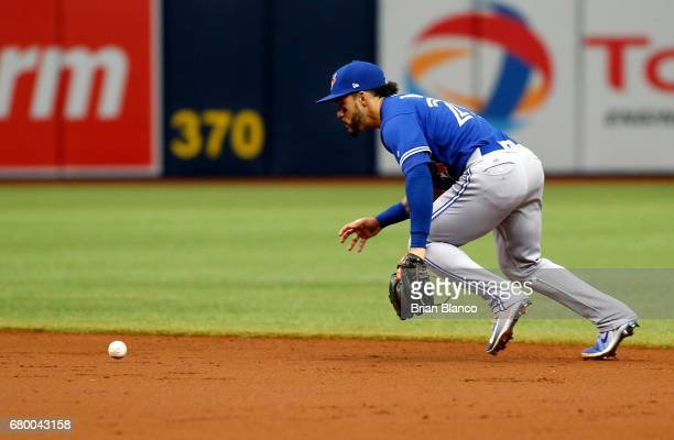 Second baseman Devon Travis of the Toronto Blue Jays attempts to recover the ball as he commits an error allowing Kevin Kiermaier of the Tampa Bay...