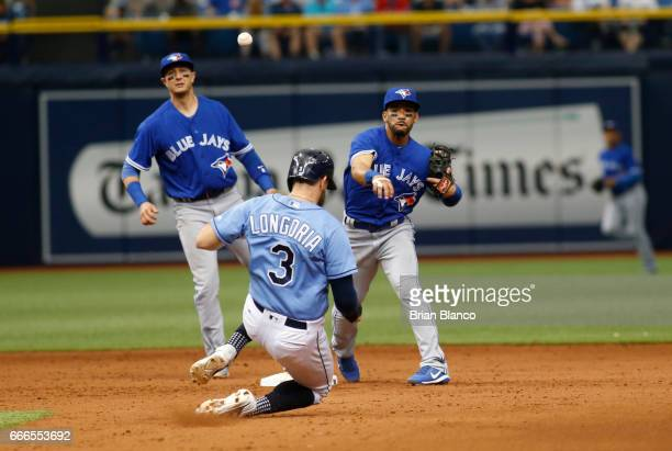 Second baseman Devon Travis of the Toronto Blue Jays gets the forced out at second base on Evan Longoria of the Tampa Bay Rays then makes the throw...