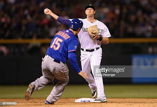 Second baseman DJ LeMahieu of the Colorado Rockies turns a double play on Travis d'Arnaud of the New York Mets on a ground ball by Ruben Tejada of...