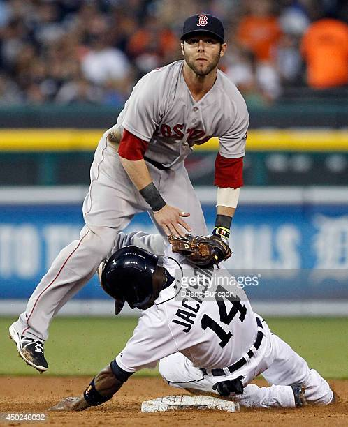 Second baseman Dustin Pedroia of the Boston Red Sox lands on Austin Jackson of the Detroit Tigers after turning the ball to get Bryan Holaday of the...