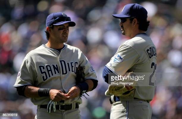 Second baseman Edgar Gonzalez and first baseman Adrian Gonzalez of the San Diego Padres await a pitching change against the Colorado Rockies in the...