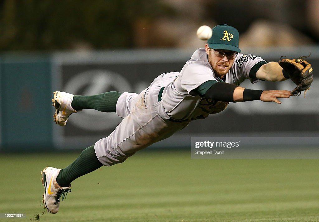 Second baseman Eric Sogard #28 of the Oakland Athletics dives but can't reach an RBI single hit by Hank Conger of the Los Angeles Angels of Anaheim in the eighth inning at Angel Stadium of Anaheim on April 10, 2013 in Anaheim, California.
