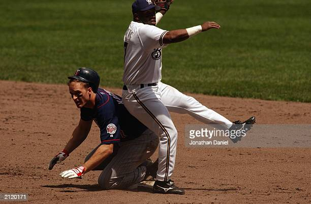 Second baseman Eric Young of the Milwaukee Brewers makes contact with third baseman Corey Koskie of the Minnesota Twins during the interleague game...
