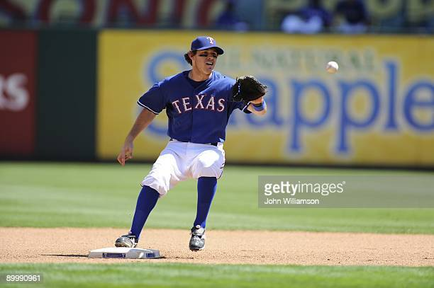 Second baseman Ian Kinsler of the Texas Rangers fields his position as he catches a throw at second base for the first out of a double play during...