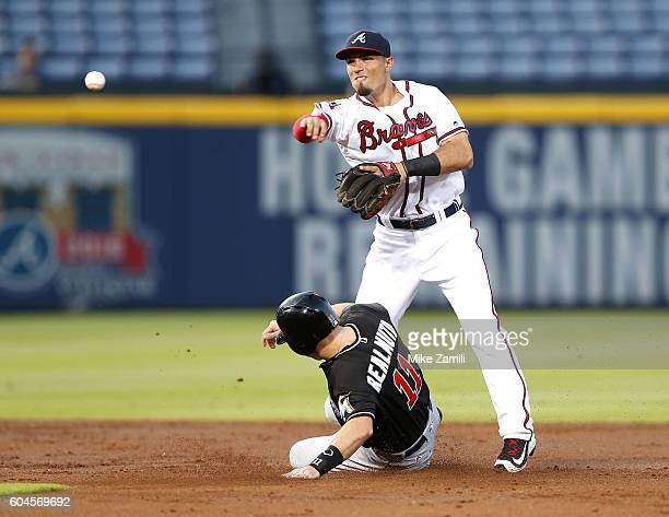 Second baseman Jace Peterson of the Atlanta Braves throws to first base over catcher JT Realmuto ##11 of the Miami Marlins in the second inning...