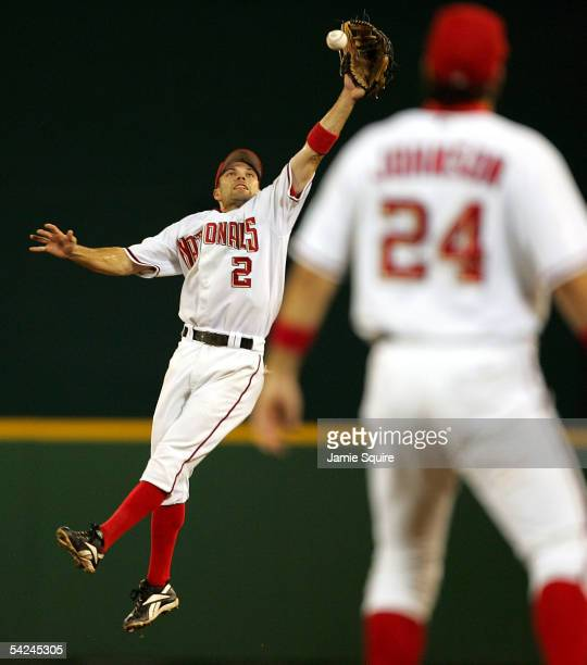 Second baseman Jamey Carroll of the Washington Nationals leaps to snag a line drive as teammate Nick Johnson looks on during the third inning of the...