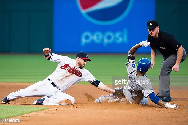 Second baseman Jason Kipnis of the Cleveland Indians tries to tag Alcides Escobar of the Kansas City Royals on a hit to left as second base umpire...