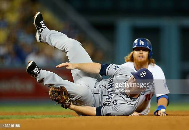 Second baseman Jedd Gyorko of the San Diego Padres falls over Justin Turner of the Los Angeles Dodgers after forcing him out a second base as part of...