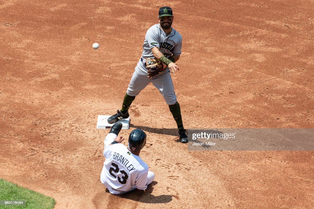 Second baseman Jose Altuve #27 of the Houston Astros makes the force out on Michael Brantley #23 of the Cleveland Indians out at second base before throwing out Edwin Encarnacion #10 at first for a double play to end the third inning at Progressive Field on May 27, 2018 in Cleveland, Ohio.