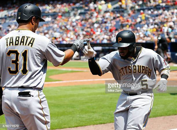 Second baseman Josh Harrison of the Pittsburgh Pirates is congratulated by teammate and right fielder Jose Tabata after Harrison scored in the fifth...