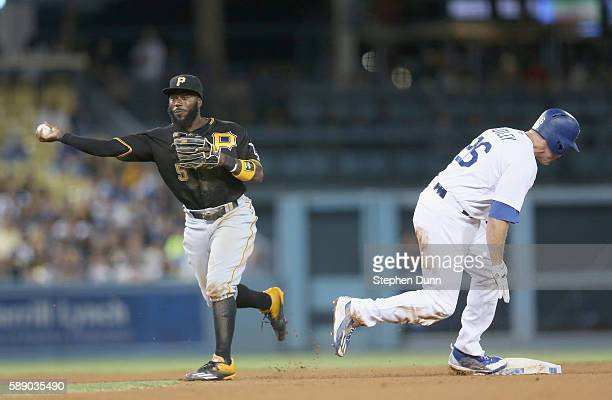 Second baseman Josh Harrison of the Pittsburgh Pirates throws to first after forcing out Chase Utley of the Los Angeles Dodgers but is too late to...