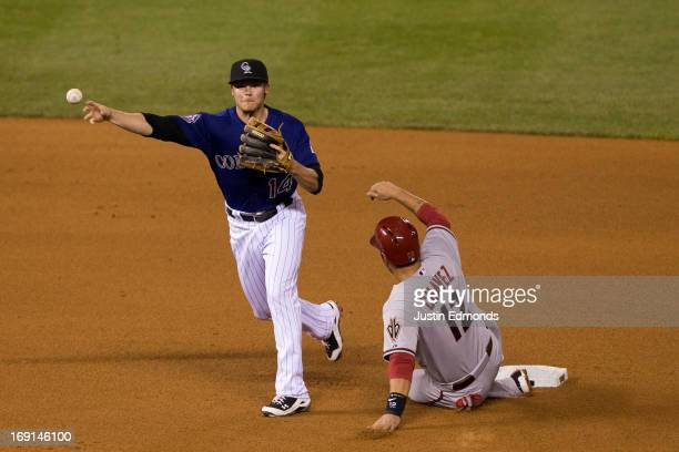 Second baseman Josh Rutledge of the Colorado Rockies is unable to complete the double play as Eric Chavez of the Arizona Diamondbacks slides in to...