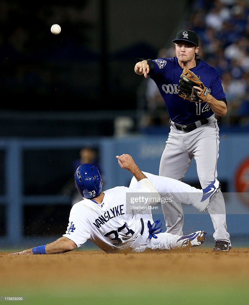 Second baseman Josh Rutledge #14 of the Colorado Rockies throws to first after forcing out Scott Van Slyke #33 of the Los Angeles Dodgers to complete a double play ending a bases loaded threat in the seventh inning at Dodger Stadium on July 11, 2013 in Los Angeles, California.