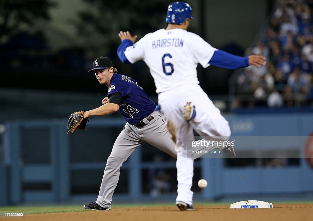 Second baseman Josh Rutlege #14 of the Colorado Rockies can't reach a throwing error by shortstop Troy Tulowitzki on a potential double play as Jerry Hairston Jr. #6 jumps over the ball in the eighth inning at the Los Angeles Dodgers at Dodger Stadium on July 11, 2013 in Los Angeles, California.