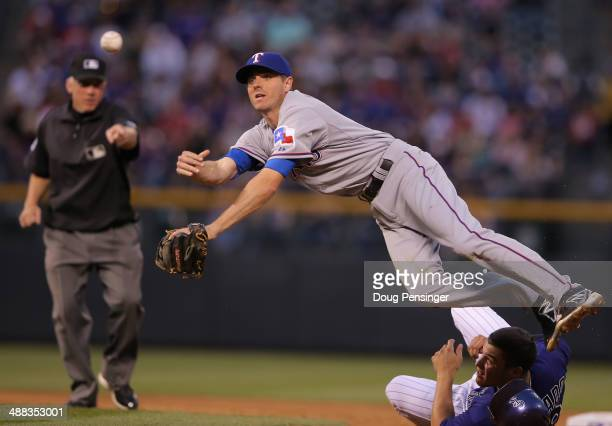 Second baseman Josh Wilson of the Texas Rangers turns a double play tagging out Nolan Arenado of the Colorado Rockies and throwing to first for the...