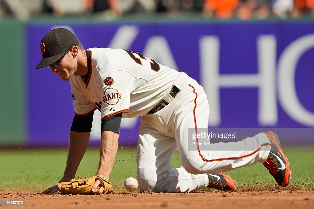Second baseman Kelby Tomlinson #37 of the San Francisco Giants can't get a handle on a ground ball for an error allowing Jose Reyes of the Colorado Rockies to reach first base in the third inning at AT&T Park on October 4, 2015 in San Francisco, California, during the final day of the regular season. The Rockies won 7-3.