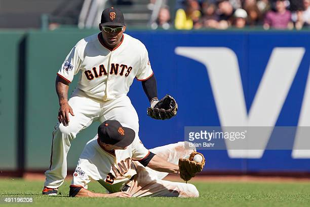 Second baseman Kelby Tomlinson of the San Francisco Giants catches a pop-up by second baseman DJ LeMahieu of the Colorado Rockies as right fielder...