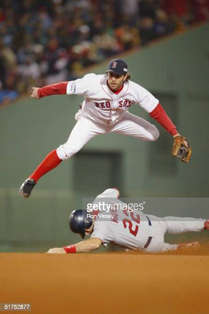 Second baseman Mark Bellhorn of the Boston Red Sox attempts the double play as Mike Matheny of the St. Louis Cardinals slides into second base during...