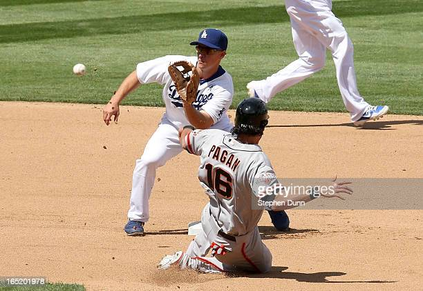 Second baseman Mark Ellis of the Los Angeles Dodgers takes the throw to tag out Angel Pagan of the San Francisco Giants trying to steal second to end...