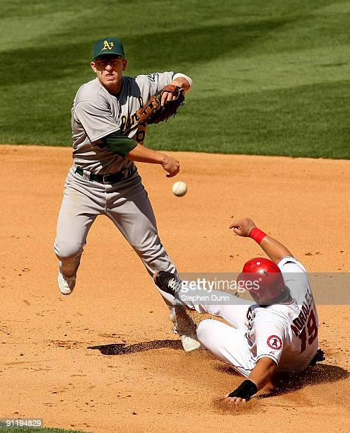 Second baseman Mark Ellis of the Oakland Athletics throws to first to complete a double play after forcing out Kendry Morales of the Los Angeles...