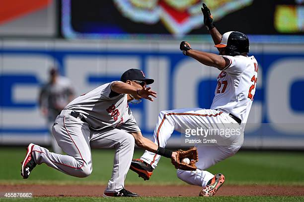 Second baseman Mookie Betts of the Boston Red Sox cannot make a tag on Delmon Young of the Baltimore Orioles as he steals second base in the first...