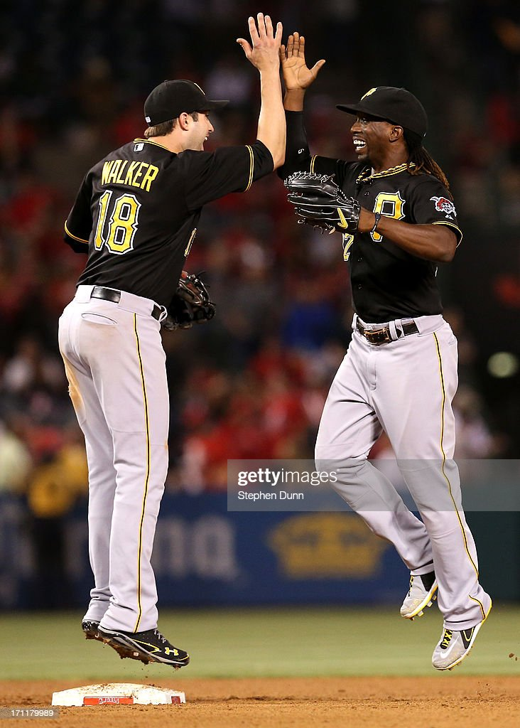 Second baseman Neil Walker #18 and center fielder Andrew McCutchen #22 of the Pittsburgh Pirates celebrate after the game against the Los Angeles Angels of Anaheim at Angel Stadium of Anaheim on June 22, 2013 in Anaheim, California. The Pirates won 6-1.