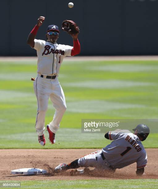 Second baseman Ozzie Albies of the Atlanta Braves jumps for a throw while left fielder Gregor Blanco of the San Francisco Giants slides into second...