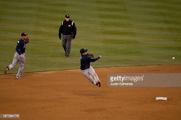 Second baseman Ramiro Pena of the Atlanta Braves makes a leaping throw to first base but is unable to beat out the infield single by Eric Young Jr of...