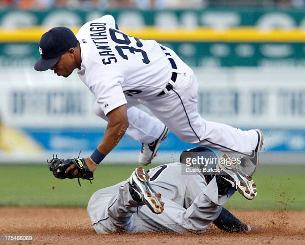 Second baseman Ramon Santiago of the Detroit Tigers is upended in a failed attempt at tagging out Alejandro De Aza of the Chicago White Sox stealing...