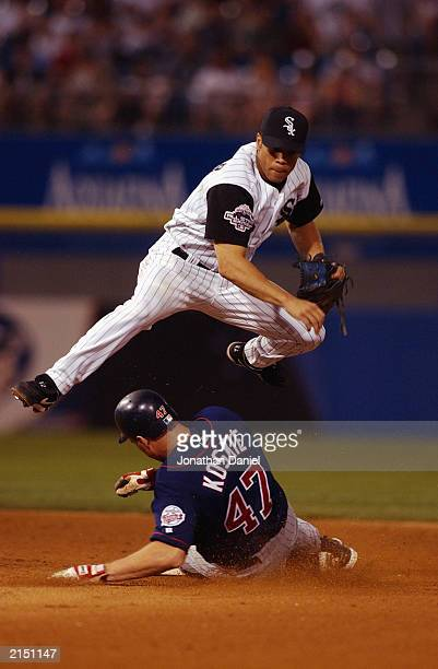 Second baseman Roberto Alomar of the Chicago White Sox turns a double play in the 12th inning forcing out third baseman Corey Koskie of the Minnesota...