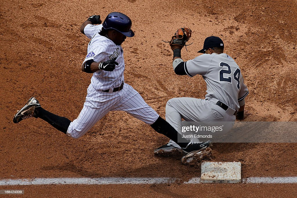 Second baseman Robinson Cano #24 of the New York Yankees falls to the ground but is able to make the catch for an out on a bunt attempt by Eric Young Jr. #1 of the Colorado Rockies during the third inning at Coors Field on May 9, 2013 in Denver, Colorado.