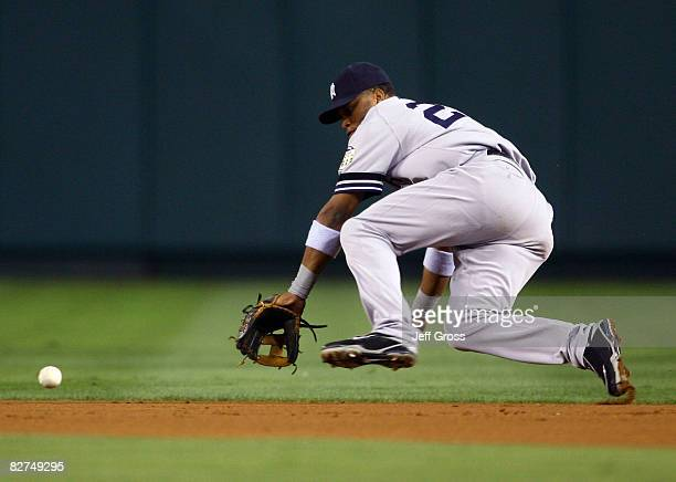 Second baseman Robinson Cano of the New York Yankees lunges for a ball hit by Reggie Willits of the Los Angeles Angels of Anaheim in the first inning...
