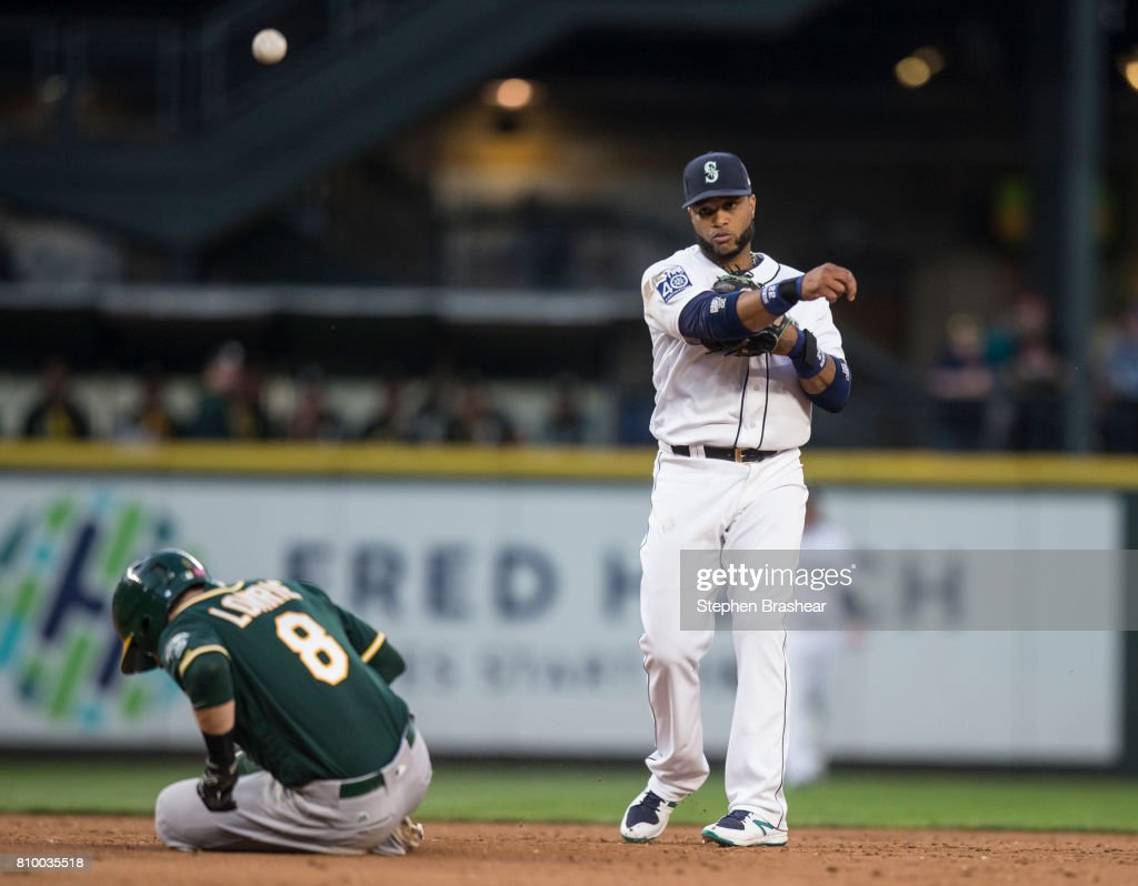 Second baseman Robinson Cano #22 of the Seattle Mariners turns a double play after forcing out Jed Lowrie #8 of the Oakland Athletics on a ball hit by Ryon Healy #25 of the Oakland Athletics during the fifth inning of a game at Safeco Field on July 6, 2017 in Seattle, Washington. The Athletics won 7-4.