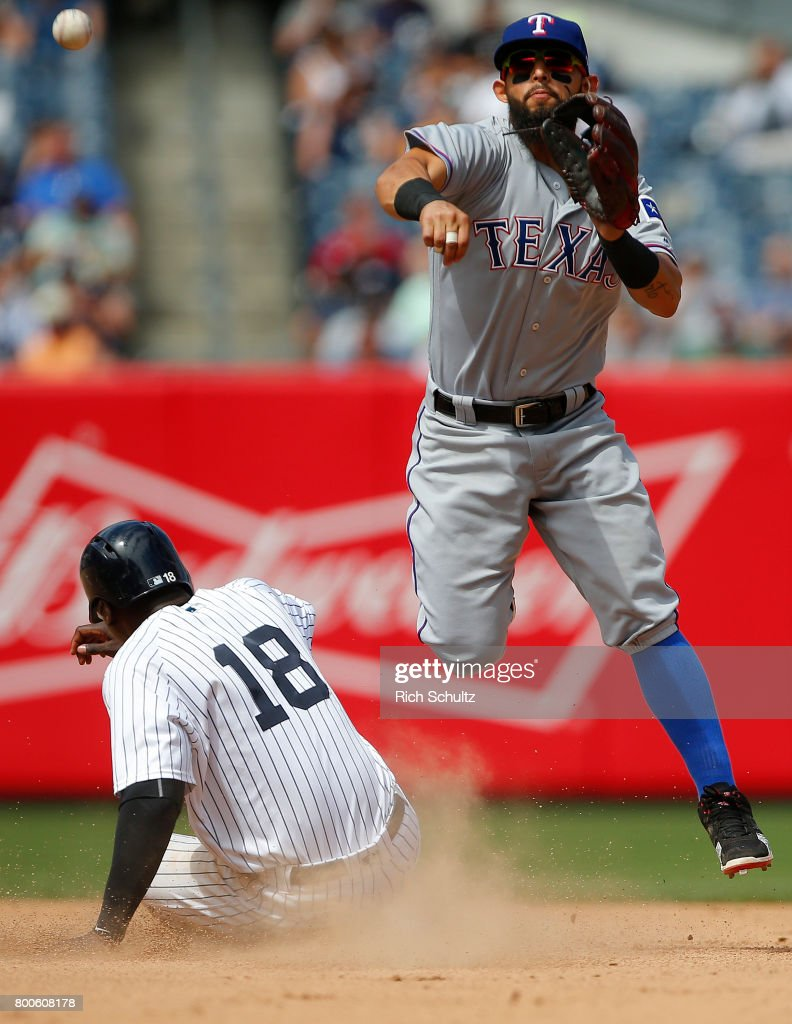 Second baseman Rougned Odor #12 of the Texas Rangers gets the force out on Didi Gregorius #18 of the New York Yankees and throws to first to complete a double play on a ball hit by Tyler Austin #26 during the seventh inning of a game at Yankee Stadium on June 24, 2017 in the Bronx borough of New York City. The Rangers defeated the Yankees 8-1.