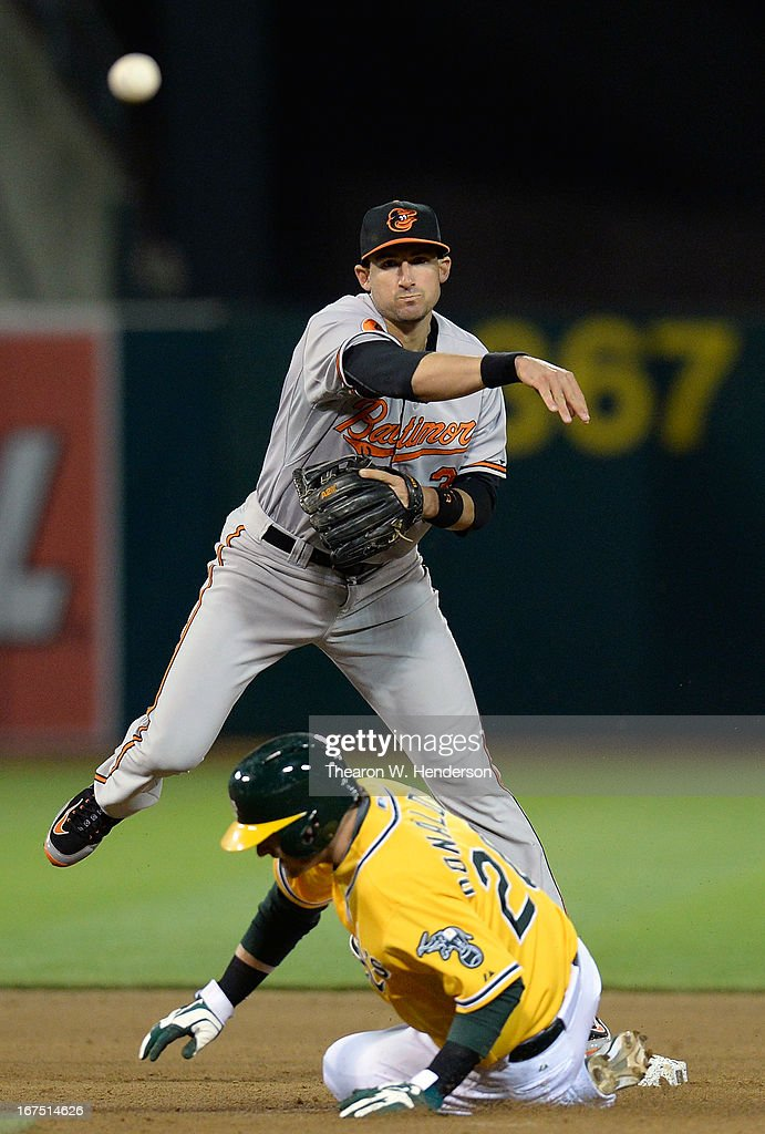 Second baseman Ryan Flaherty #3 of the Baltimore Orioles gets his throw off to complete the double-play over Josh Donaldson #20 of the Oakland Athletics in the fifth inning at O.co Coliseum on April 25, 2013 in Oakland, California.