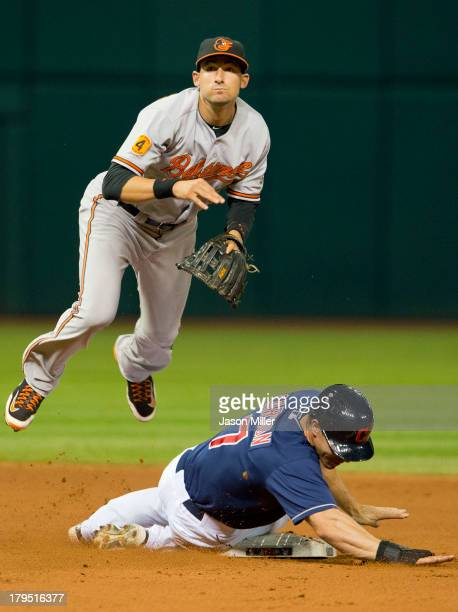 Second baseman Ryan Flaherty of the Baltimore Orioles jumps over Matt Carson of the Cleveland Indians after throwing to first for the double play...