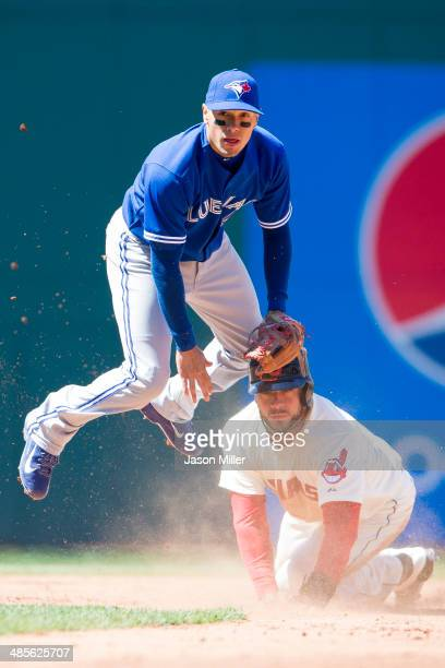 Second baseman Ryan Goins of the Toronto Blue Jays jumps over Mike Aviles of the Cleveland Indians after throwing to first for a double play off a...