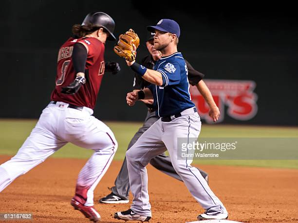 Second baseman Ryan Schimpf of the San Diego Padres covers first base and makes the out against Tuffy Gosewisch of the Arizona Diamondbacks in the...